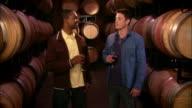 MS Two men drinking wine and toasting near casks in wine cellar / Paso Robles, California, USA