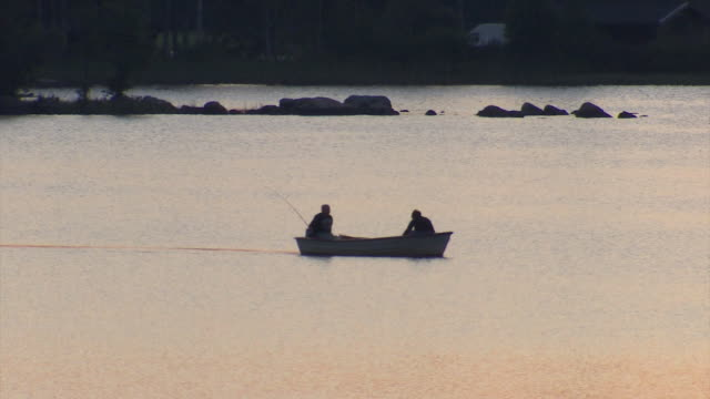 Two men fish from a small boat on a lake in the Ekero area of Sweden.