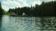 SLO MO WS Two men fishing from canoe on scenic lake surrounded by evergreen trees, Morristown, Vermont, USA