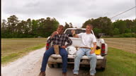 Two men have lunch on the tailgate of a pickup truck.