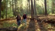 Two men hiking in woods wearing backpacks
