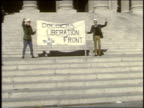Two men holding Soldiers Liberation Front banner on steps of federal building / Washington DC United States