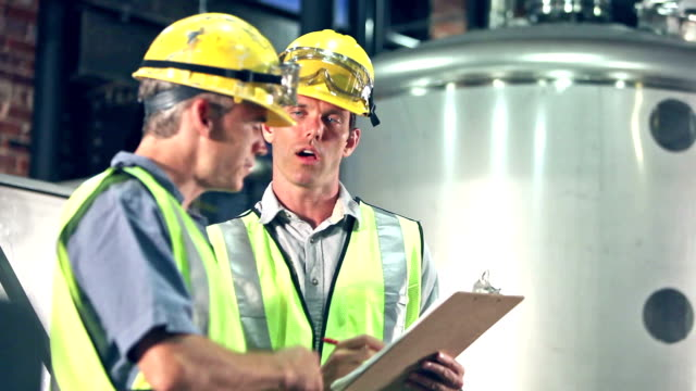 Two men in factory talking by storage tanks