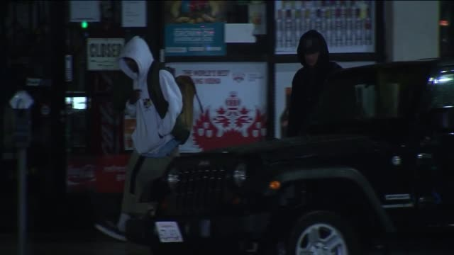 Two men in hooded sweatshirts walk in the streets of Los Angeles at night