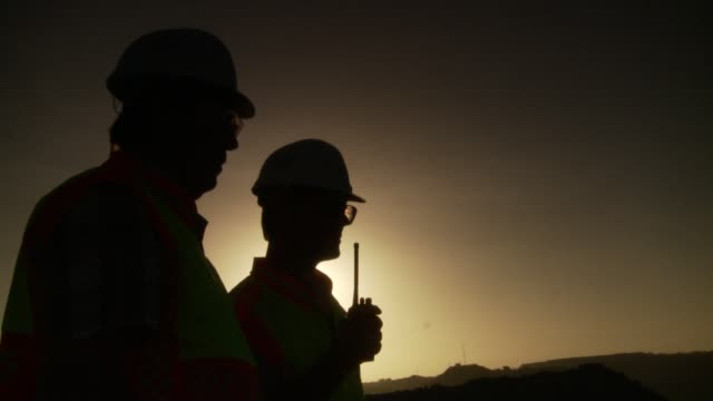 Two men in silhouette stand over a project discussing work issues. Available in HD.