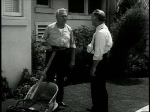 1940 WS two men in yard speaking about homeowners' rights, one with hand on lawn mower / United States