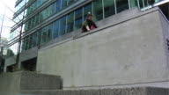 MS LA PAN Two men jumping over building ledge and running away onto street, performing parkour, Vancouver, British Columbia, Canada