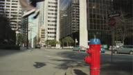 MS Two men jumping over fire hydrant, performing parkour, Vancouver, British Columbia, Canada