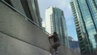 MS LA Two men jumping up and over building ledge, performing parkour, Vancouver, British Columbia, Canada