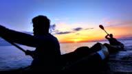 SLO MO zwei Männer Kajakfahren bei Sonnenuntergang