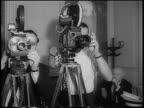 B/W 1966 two men operating film cameras indoors / newsreel