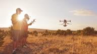 DS-zwei Männer, die die Drohne auf Hügel bei Sonnenuntergang in Betrieb