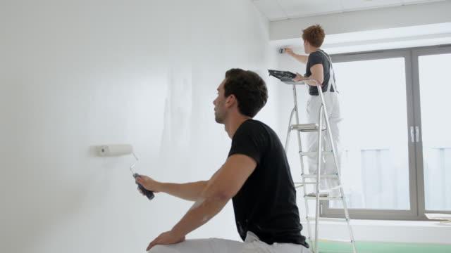 MS Two men painting wall / London, England, United Kingdom
