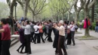 WS two men practice dance moves in Fuxin Park in Shanghai China on Sunday April 10 MS people dancing in pairs in Fuxin Park Shanghai China