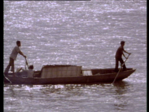 Two men punting long wooden boat on glittering river Ho Chi Minh