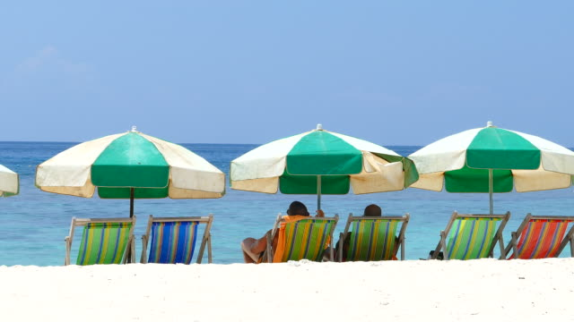 Two Men Relaxing on Beach Chairs at Summer Beach