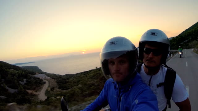POV Two men riding a scooter at sunset