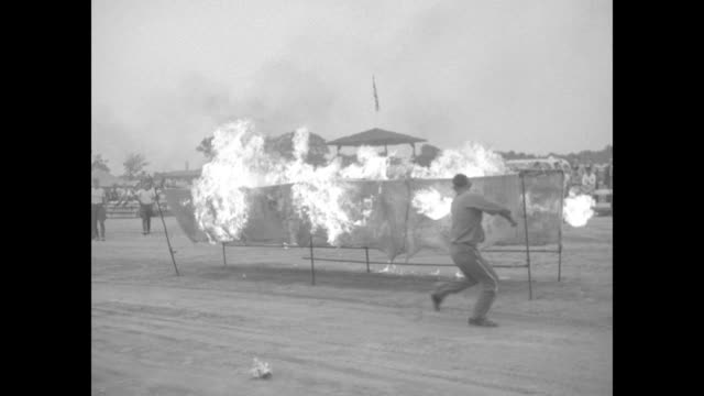 Two men run on opposite sides of an open chute setting fire to its sides motorcycle approaches the chute drives through it during stunt competition...