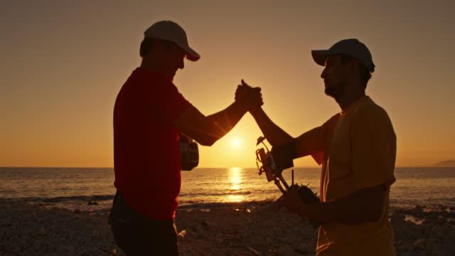 Twee mannen schudden handen op de landing van de drone op strand