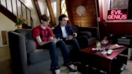 MS Two men sitting on sofa playing video game/ Woman running down stairs and jumping onto men's laps/ Los Angeles, California