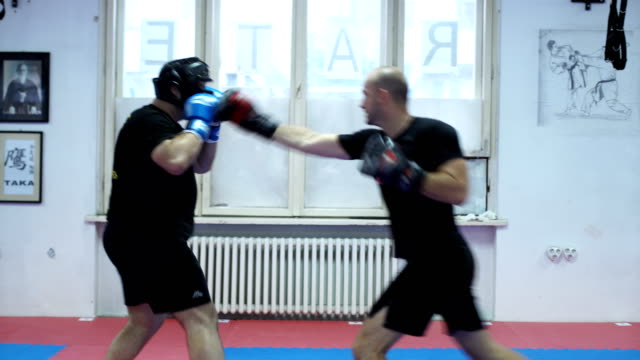 two men sparing with boxing gloves they are moving acrose a room