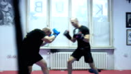 two men sparing with boxing gloves