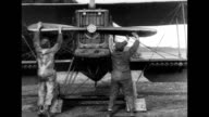 Two men turn plane propellers by hand to get it started / Cplane flies with automatic pilot / CU of the plane's mechanicals / Various early biplanes...
