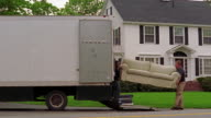 Two men unloading sofa from moving truck + walking towards house