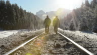 Two men walk up snow covered railway tracks