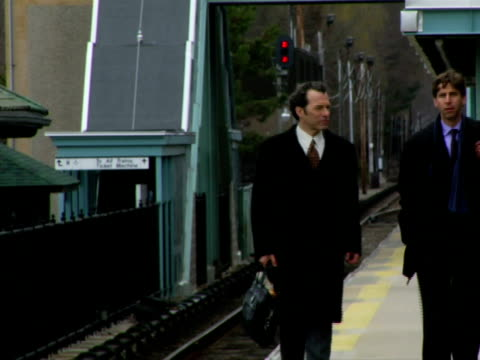 MS, Two men walking on railroad station platform, Chappaqua, New York State, USA