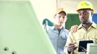 Zwei Männer arbeiten in Druckerei mit Ausrüstung