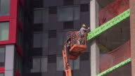 Two men working on Brooklyn building exterior using cherry picker on a sunny day.