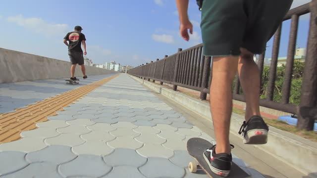 MS POV Two men's skateboarding on side walk / Chatan, Okinawa, Japan
