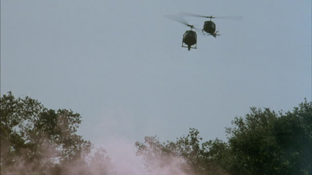 Two military helicopters land and pick up wounded soldiers.