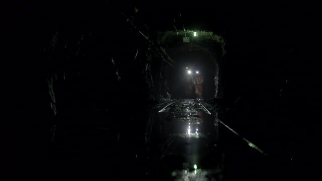 Two miners walk in mine tunnel towards camera