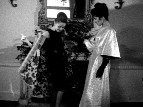 Two models admire each others clothes One wears a cocktail dress and a mink coat the other a metallic evening gown 1962