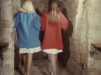 Two models wear Feraud dresses underneath brightly coloured coats