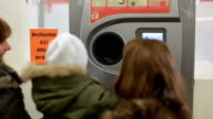 Two mother and baby girl recycling bottles at the supermarket