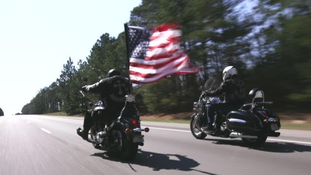Two motorcycle club members ride on highway