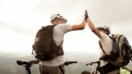SLO MO of two mountain bikers doing the high five