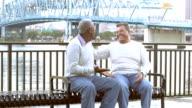 Two multi-ethnic senior men talking on park bench