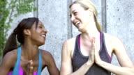 Twee multi-etnische vrouwen beoefenen van yoga, lachen