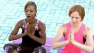 Two multi-ethnic women practicing yoga