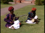 Two musicians in turbans sit on grass playing traditional Indian musical instruments Royal Tour of India; Feb 92