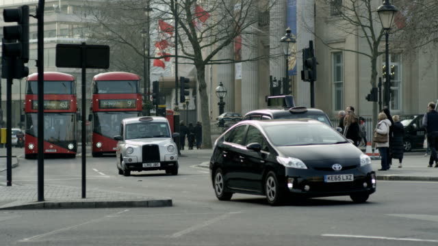 Two new red Routemaster London buses approaching traffic light together at Trafalgar Square
