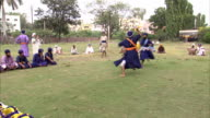 Two Nihang warriors swing swords as they go through weapons training.