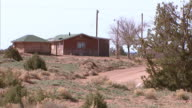 WS Two onestory red buildings house home narrow dirt road green shrubs plants utility wires poles blue sky BG Southwest arid dry desert Navajo Nation...