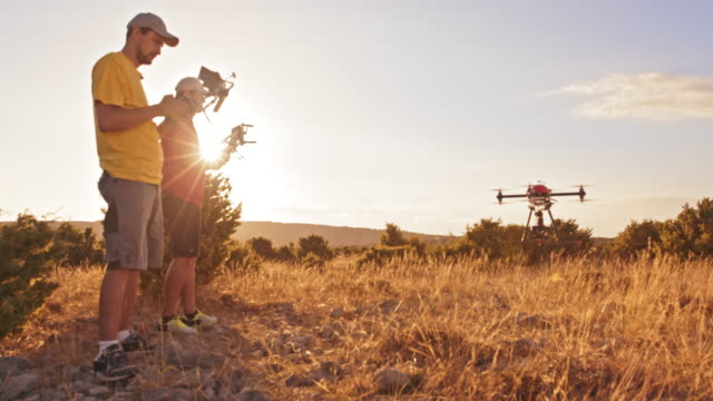 DS Two operators landing a drone on a hilltop at sunset