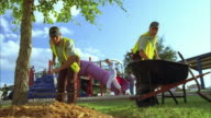 WS ZI ZO SLO MO Two park maintenance workers landscaping with mulch / Kyle, Texas, USA