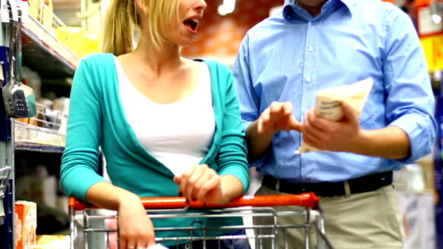Two people buying food in supermarket.
